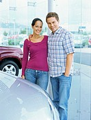 portrait of a young couple standing in a car showroom