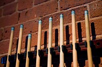 Pool cues in a rack on brick wall