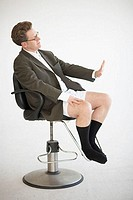 Side profile of a businessman sitting in an office chair making a stop gesture