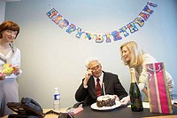 Businessman celebrating his birthday with two businesswomen