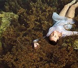 High angle view of a young woman lying in water