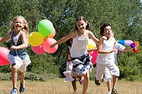 Five children playing with balloons in a park