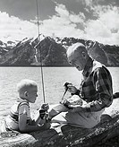 Side profile of a senior man with his grandson sitting at the lakeside