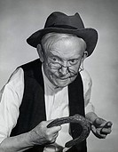 Close-up of a senior man holding a horseshoe