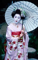 Geisha in kimono, carrying an umbrella in the garden at Maruyama-koen.  Kyoto city. Kyoto. Japan