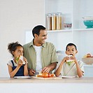 Father and two children eating sandwiches