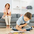 Son sitting on the floor drawing with his mother behind him