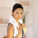 Woman with a towel around her neck after a home workout