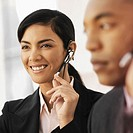 View of a businesswoman and a businessman using headsets