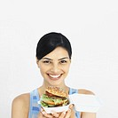 Portrait of a young woman holding a burger