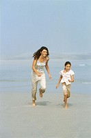 Portrait of a mother and a daughter (8-9) running on the beach