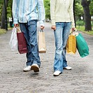Low section of a couple carrying shopping bags