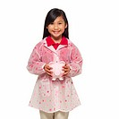front view portrait of a girl (10-11) holding a piggy bank