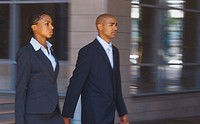 Young businesswoman and businessman walking together