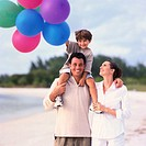 portrait of a mother and father on the beach with their son carrying balloons