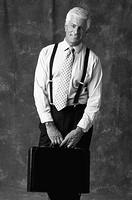 portrait of an elderly businessman standing with a briefcase (black and white)
