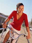portrait of a young woman riding a bicycle on a pier