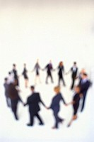 blurred high angle view of men and woman holding hands to form a circle