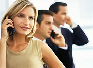close-up of woman talking on a mobile phone with two men on the phone behind her