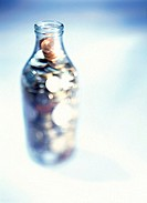 blurred close-up of a milk bottle full of coins