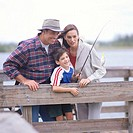 portrait of a mother and father fishing over a pier with their son
