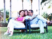 view of a mother and father sitting in garden chairs being hugged by their daughter from behind