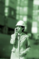 toned shot of a young woman wearing a hardhat and talking on a mobile phone