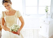 portrait of a young bridesmaid holding a bouquet of flowers