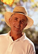 Portrait of an elderly man wearing a straw hat