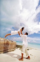 side profile of a woman jumping into a man´s arms on the beach