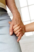 close-up of a grandfathers hand holding his grandsons