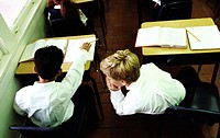 high angle view of two boys (8-10) whispering in class