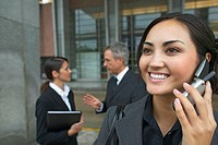 Two business executives talking in the background and a businesswoman talking on mobile phone in the foreground