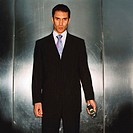 portrait of a businessman standing in an elevator holding a mobile phone