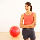 Woman in sports gear with exercise ball in background