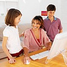 Mother using a computer with daughter (9-10) and son (11-12)