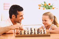 Portrait of a father and daughter (6-8) playing chess