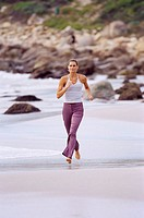 Portrait of a young woman jogging on the beach