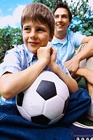 Close-up of a young boy (6-8) holding a football beside his father
