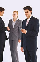 Young businessman using a mobile phone with two business executives shaking hands behind him