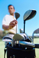 Low angle view of a man taking a golf club from a golf bag (blurred)