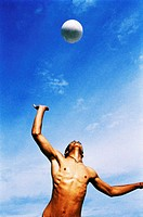 low angle view of a young bare chested man jumping to hit the volley ball