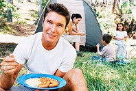 portrait of a young man eating breakfast at a campsite
