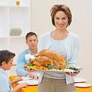 Mother holding a plate of roast chicken and vegetables with her family in the background