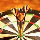 Close-up of dartboard with three darts on the bulls eye