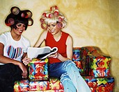 two young woman with curlers in their hair reading a magazine