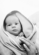 Baby (3-6 months) wrapped in a blanket held by an adult (black and white)