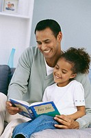 Close-up of father reading story to daughter (8-9)