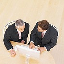 Elevated view of two businessmen working on computer