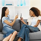 Side view of two young women sitting on sofa and holding mobile phones